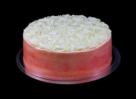 One red cake decorated with buttercream icing and pearls isolated on black Standard-Bild