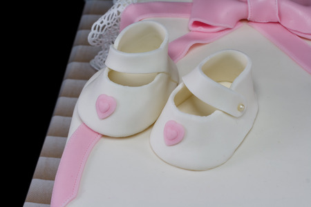One white cake in the shape of a baby dress isolated on black