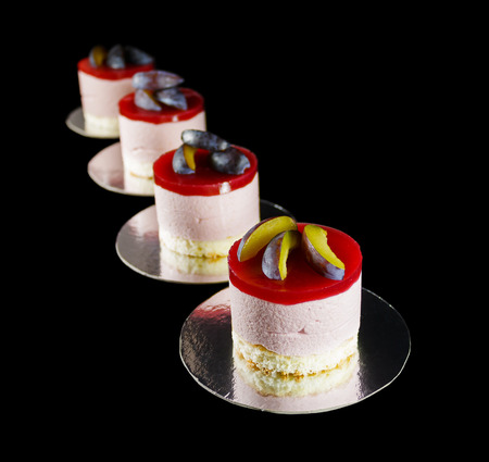 Four small cakes decorated with plum wedges isolated on black