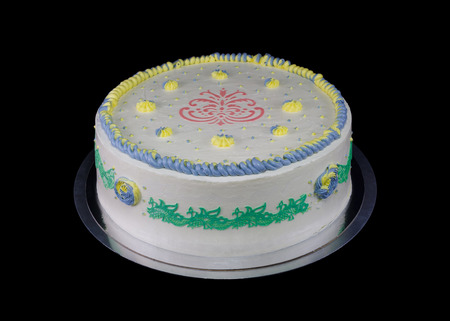 One white cake with decorations in different colors isolated on black
