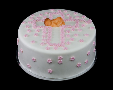 One white cake decorated with a newborn baby and pink flowers isolated on black