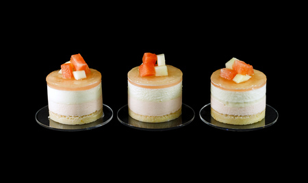 small cake: Three small cake decorated with different fruits isolated on black