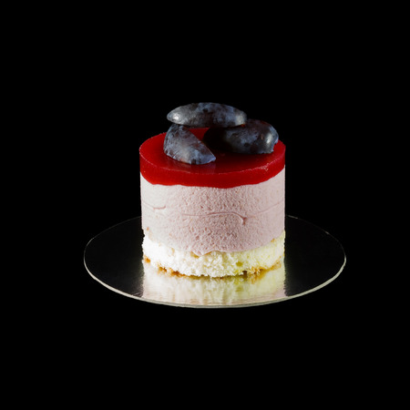 small cake: One small cake decorated with plum wedges isolated on black Stock Photo