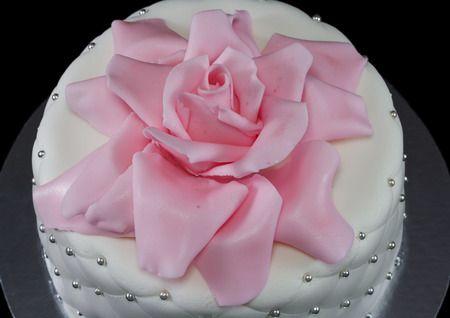 One white cake decorated with a pink rose and pearls isolated on black Standard-Bild