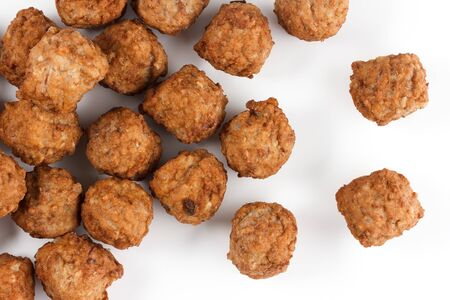 Close-up of lots of meatballs from above on a white background