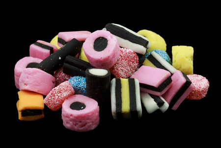 One pile of liquorice allsorts candy isolated on black background, lots of different shapes and colors Standard-Bild
