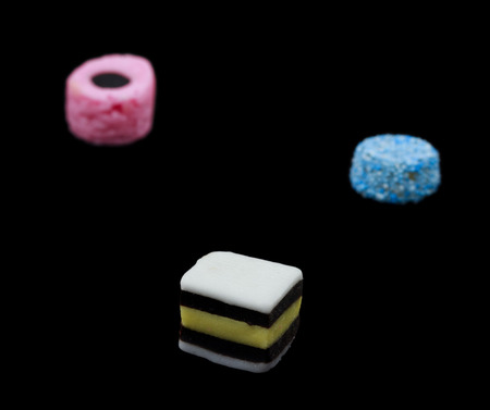 liquorice: Three liquorice allsorts candy isolated on black background, one in focus and two out of focus