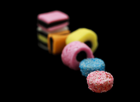 Seven liquorice allsorts candy isolated on black background, one in focus and the rest out of focus