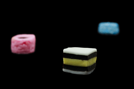 Three liquorice allsorts candy isolated on black background, one in focus and two out of focus