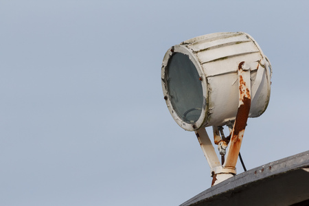 Marine signal light with rust on a boat used as a search light or signaling
