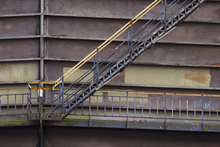 Industrial ladder on a big brown silo in metal