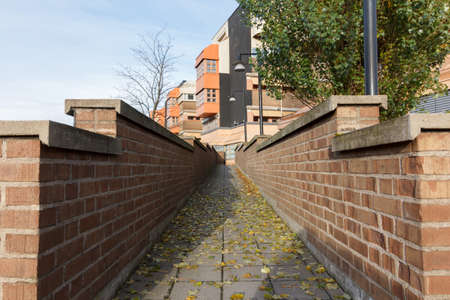 Concrete pathway with brick walls and leaves on the ground in autumn