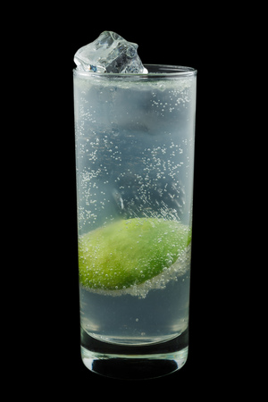 lime juice: Gin Rickey, consisting of gin, lime juice and soda water. Isolated on black background. Stock Photo