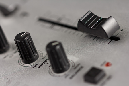 fader: Two knobs and a fader of a DJ mixer with metal surface Stock Photo