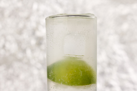 Gin Rickey, consisting of gin, lime juice and soda water. Light gray background with some bokeh.