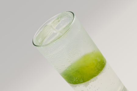lime juice: Gin Rickey, consisting of gin, lime juice and soda water. Light gray background. Stock Photo