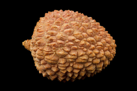 lichee: Side view of one lychee fruit Litchi chinensis, also known as litchi, liechee or lichee, isolated on a black background