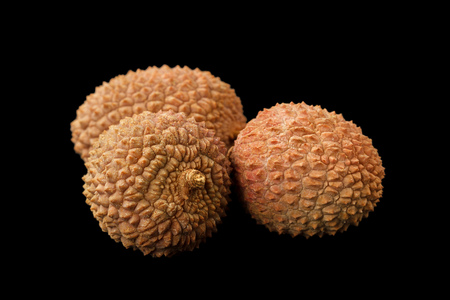 lichee: Three lychee fruits Litchi chinensis, also known as litchi, liechee or lichee, isolated on a black background Stock Photo