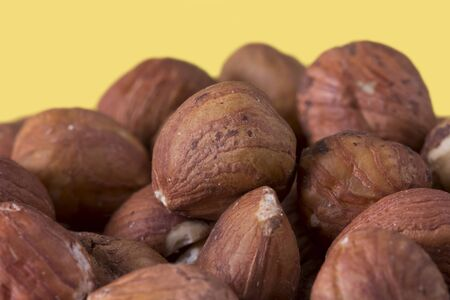 Bunch of hazelnuts against a yellow background