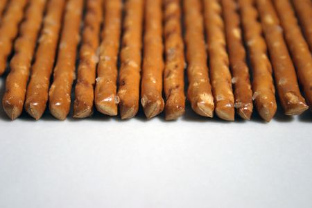 Savoury sticks placed in row on white background - closeup.