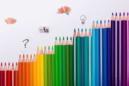 The light bulb and question mark as symbols of creativity, thinking and solution finding. Sketching or drawing techniques are often used while brainstorming or creating a mind map. Color pencils are arranged in stages, just like in video games, symbolizing the ongoing process of creativity and working successfully towards a solution.
