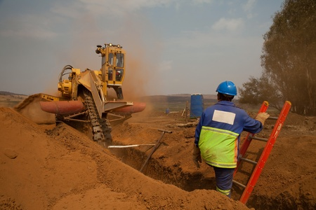 trencher: Construction worker watching a trencher machine digging and trench for a pipeline