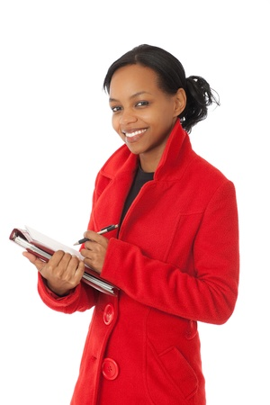 African American business woman with warm red winter coat holding notebook and pen photo