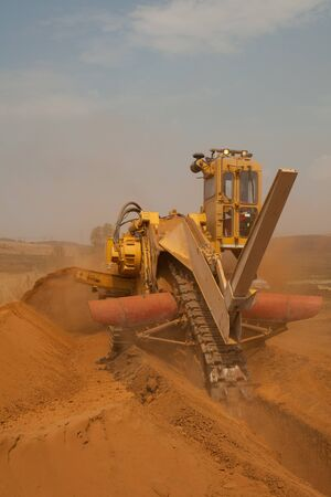 trenching: Yellow trencher digging a deep pipeline trench on construction site