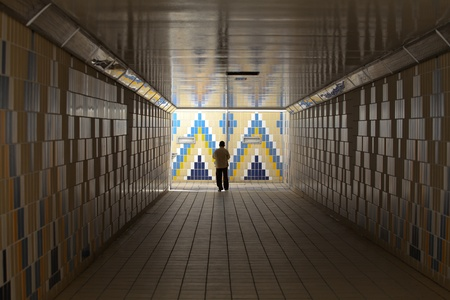 Man walking and standing in an patterned tiled underpass tunnell photo