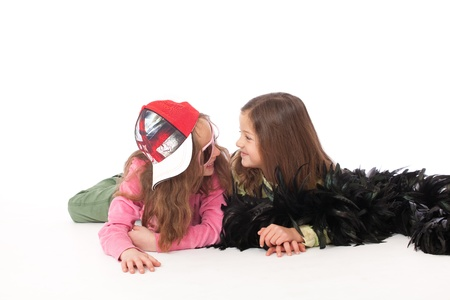 Two freinds looking and smiling and lying isolated with cap and feather boa Stock Photo - 9478091