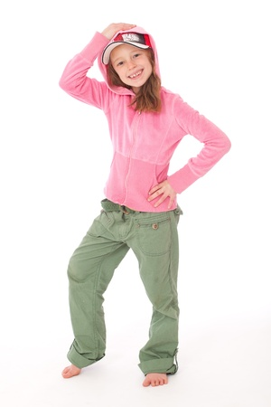 little girl posing: Sporty girl in pink top and green trousers with cap and hood and hand on head