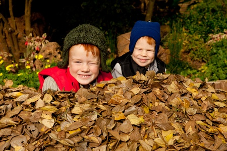 lying in leaves: Two happy smiling brothers sit in a heap of colorful autum leaves wearing warm clothes and hats in a park or garden setting