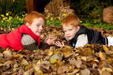 Two happy smiling brothers or sons are lying facing each other in a pile of yellow and brown autumn / fall leaves in a colorful garden or park photo