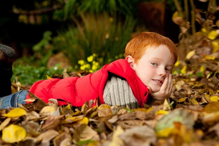 A happy young red haired boy is lying in a pile of colorful autumn  fall leaves in a garden or park setting, with chin resting on hand and smiling photo