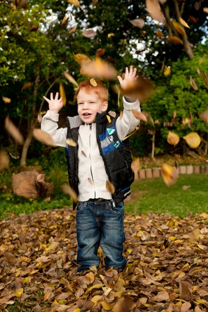 Happy red haired young boy is playing and throwing  the autumn leaves in a colorful park or garden photo