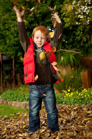 Happy red haired young boy is playing by throwing  the autumn leaves high in the air, in a colorful park or garden photo