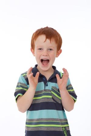 Garçon de la tête rouge avec des taches de rousseur regardant choqués et surpris tout souriant et tenant par la main dans l'air Banque d'images
