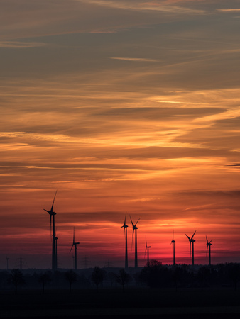 Wind power plants at sundown with colorful clouds and sky