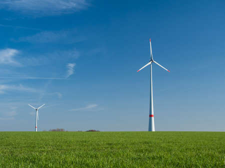 two wind power plants on a green meadow and sunny weather