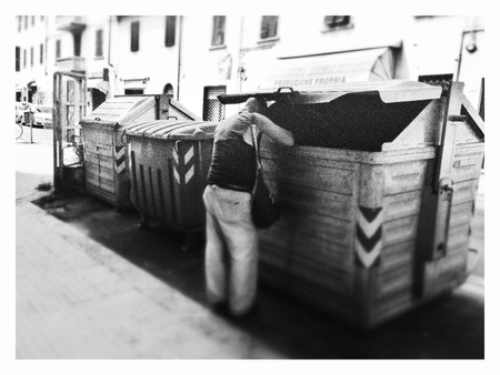 dumpster: Poor man looking inside a dumpster