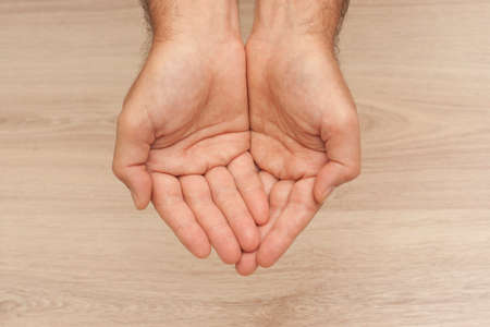 Hands cupped togheter on a wooden background
