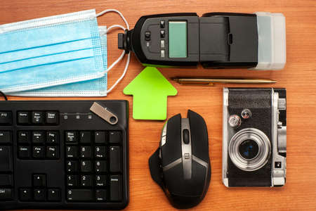 Flat assembly composition with a mask, keyboard flash mouse pen USB pen block notes and flash on wooden background