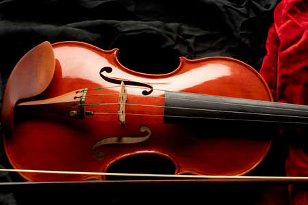 Close up of a violin with bow on a background of black and red fabrics