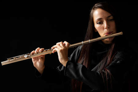 A beautiful young woman play a golden flute