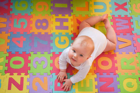 Cute baby looking up from colorful alphabet mat while playing on tummy. Foto de archivo