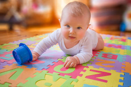 Cute baby in white vest, reaching for cups while on lying on tummy on alphabet mat.