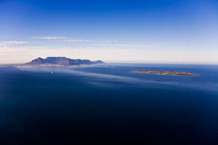Aerial view of Robben Island with Table Mountain in the distance, Cape Town; South Africa. Former South African President, Nelson Mandela, was held here as a political prisoner for 27 years.