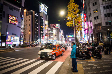 TOKYO - DECEMBER 31, 2016: A man is waiting to cross the street at Ginza District December 31, 2016 in Tokyo, Japan. Ginza extends for 2.4 km and is one of the worlds best known shopping districts.