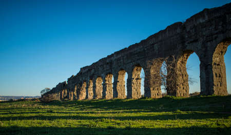 Roman aqueduct ancient ruins in Italy at sunset