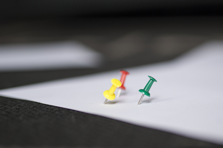 Set of push pins in different colors, with real shadows, isolated on white background. (Selective Focus)